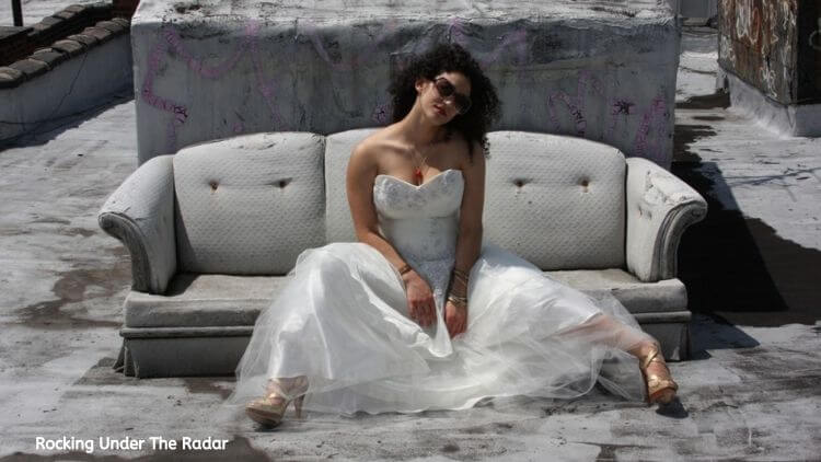Musician Tammy Infusino sitting on a grey couch in a white dress | Eat Sleep Breathe Music