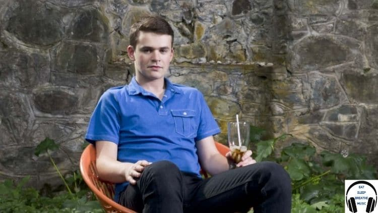 Gabe Goodman White man sitting in a orange chair with a drink in his hand   Song of the Day Feature