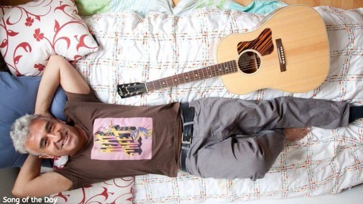 The Musician Leonino Laying in a Bed next to a guitar| Eat Sleep Breathe Music