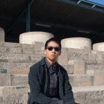 Rock Musician Eddy Yang Sitting On A Bench with Sunglasses | Eat Sleep Breathe Music