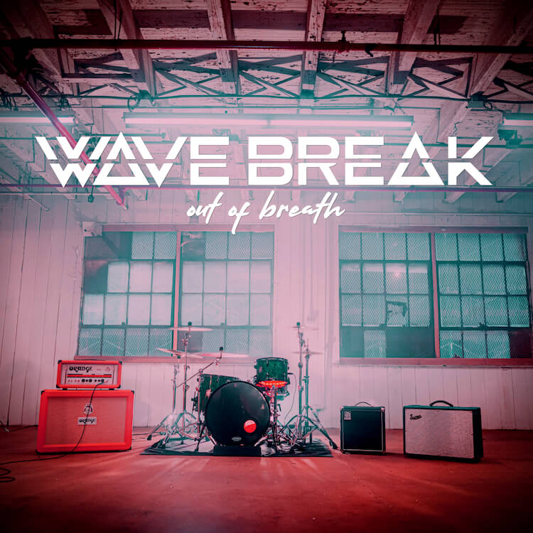 """Warehouse of Band set up with Amps drums, and guitars with the words """"Wave Break"""" and """"Out of Breath"""" 