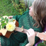 Stephanie Catlett Sitting in a chair with a guitar | Eat Sleep Breathe Music
