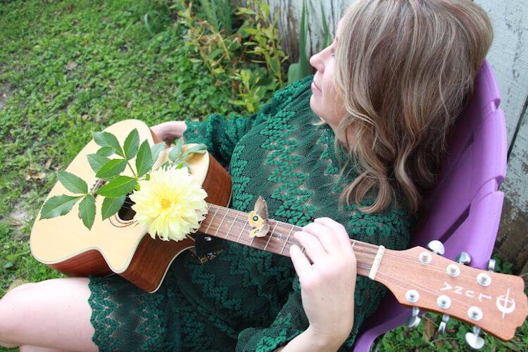 Stephanie Catlett Sitting in a chair with a guitar | Eat Sleep Breathe Music