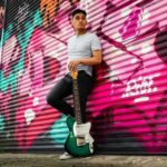 Darro Chea Dark Haired Man Wearing A Grey Shirt and Black Pants holding a guitar standing against a pink spray painted garage wall | Eat Sleep Breathe Music