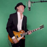 White Man Playing the Guitar in a black suit with a black hat against a green screen Sun Dogs Song of the Day | Eat sleep Breathe Music