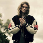 Man with shoulder length blond hair wearing a black jacket with white sleeves and pink flowers on the side with hands held in front of his face | Kid Lab Rat Song of the Day | Eat Sleep Breathe Music
