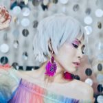 Woman with White Hair and a Rainbow Shirt against a background of sequins | Eat Sleep Breathe Music