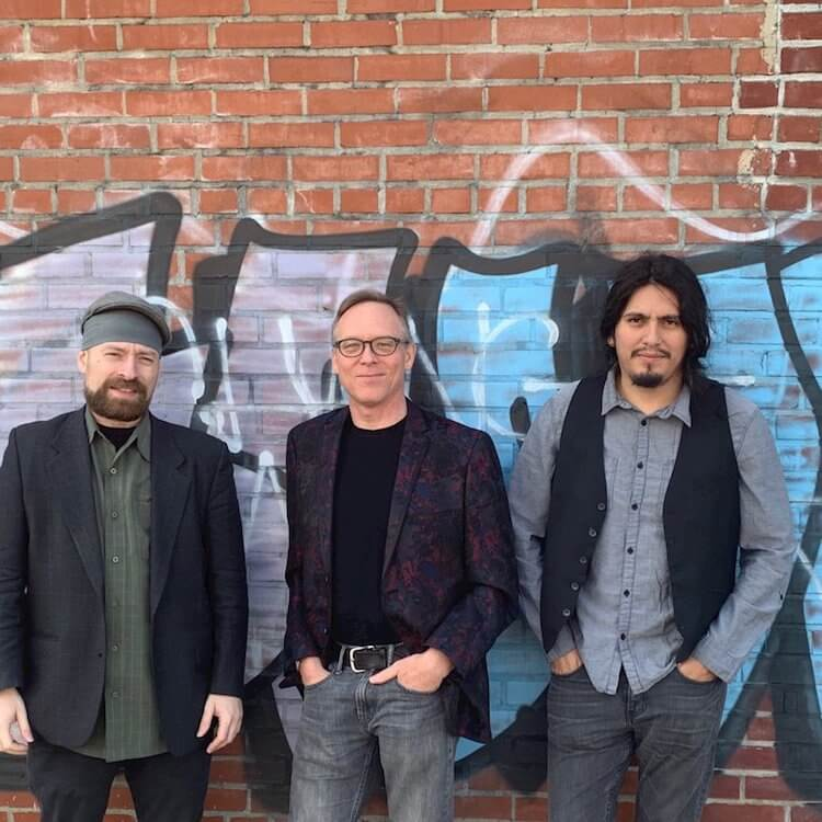 Three Men Standing Against a Brick Wall with Graffiti |Bushwick Booze Band | Eat Sleep Breathe Music