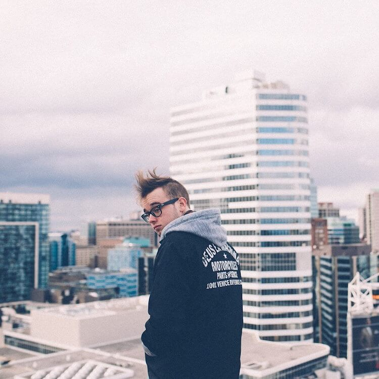 White Man on a Roof with his back turned to us wearing a hoodie in front of a high rise | Erich Mrak song of the day| Eat Sleep Breathe Music