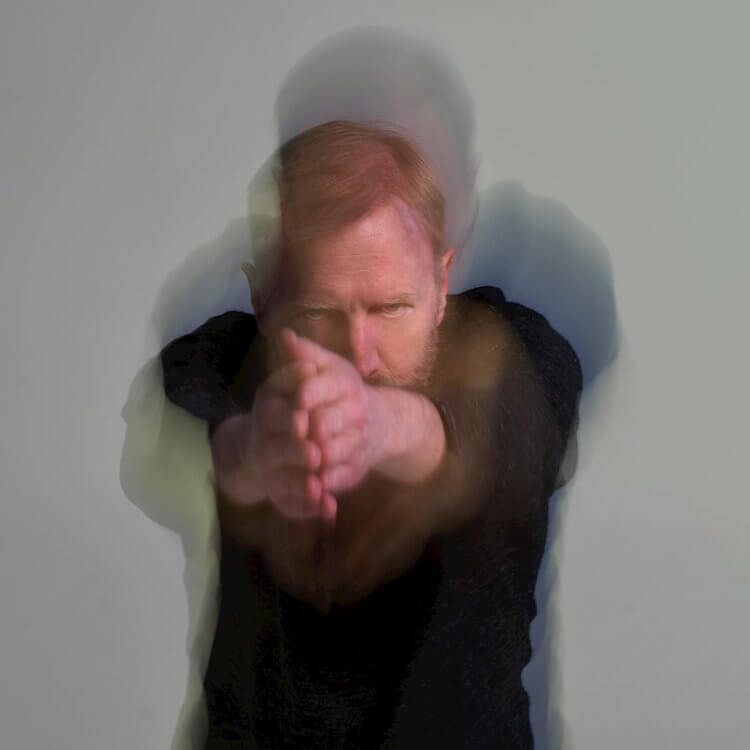White Man in a blurry photo with his arms pointing in front of him |Lost American| Eat Sleep Breathe Music