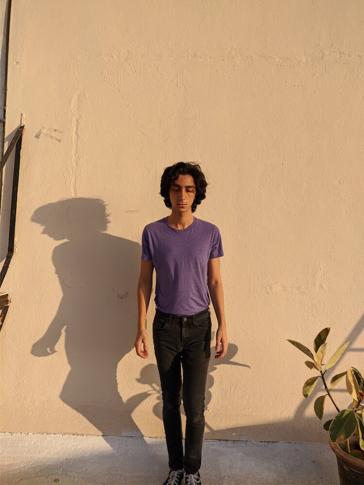 Mikhail Cazi in front of a beige wall with purple shirt and dark pants | Song of the Day| Eat Sleep Breathe Music