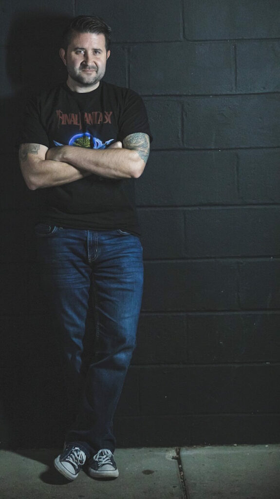 White Man standing against wall with arms crossed wearing black tshirt and jeans | Red Skies Mourning Song of the Day | Eat Sleep Breathe Music