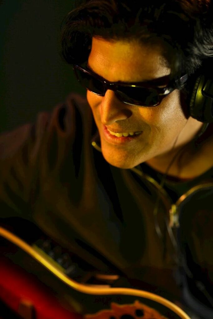 Nonviolenze AKA Shri Baratan Man Wearing Sunglasses and Playing a guitar | Eat Sleep Breathe Music