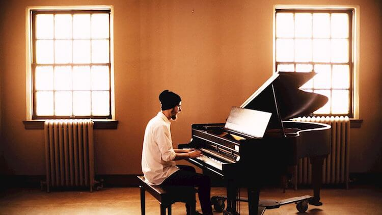Ryan Summers Sons of Gallow Song of the Day Man In White Shirt Playing a Piano In a White Walled Apartment with a Window to the Left and Right   Eat Sleep Breathe Music