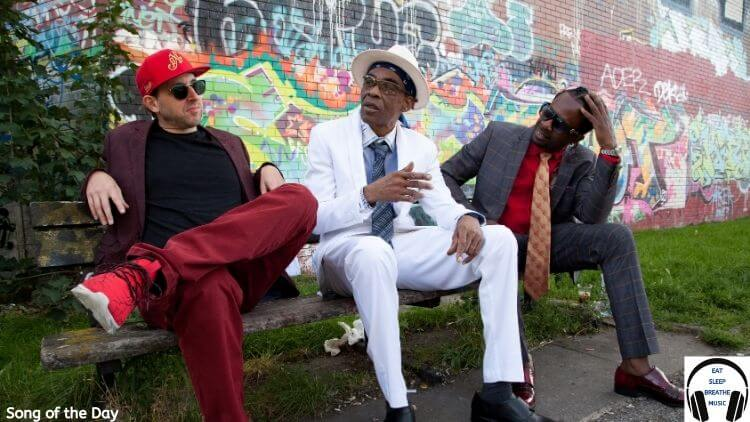"""A white man, a black man and 3rd black man are sitting on a bench in suits in front of a graffiti'd wall