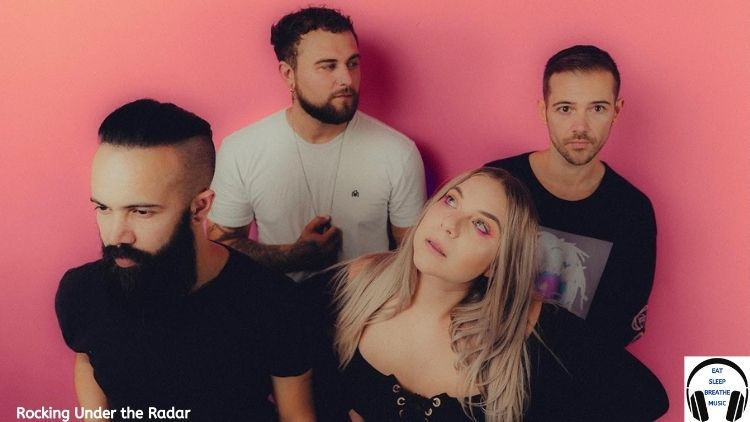 The Rivals Band One guy with a beard, a blonde girl, a guy with a beard and a another guy in front of a pink wall | Rivals Rocking Under the Radar Feature | Eat Sleep Breathe Music