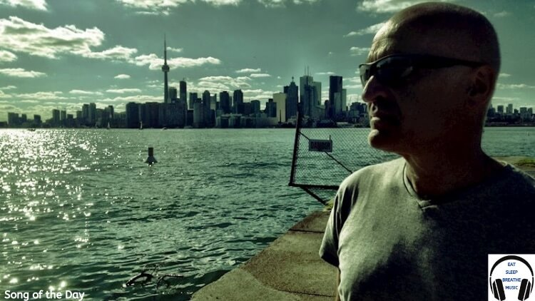 Singer Chris Birkett In front of the water with a city behind it