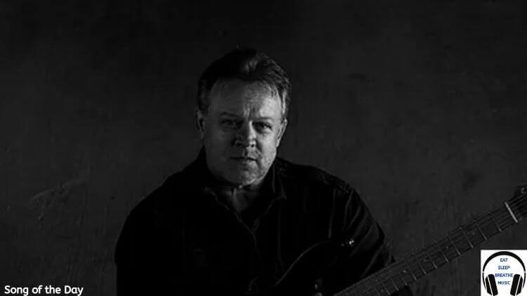 TIm Haverman of SD17 wearing a black shirt holding a guitar